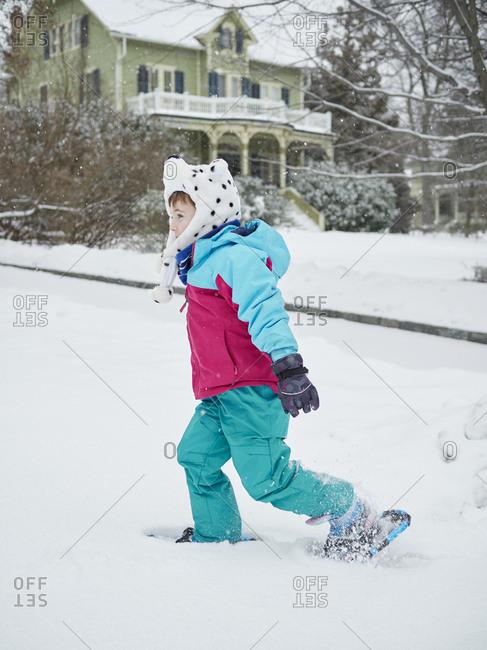 Boy in bear hat wearing snowshoes in front yard