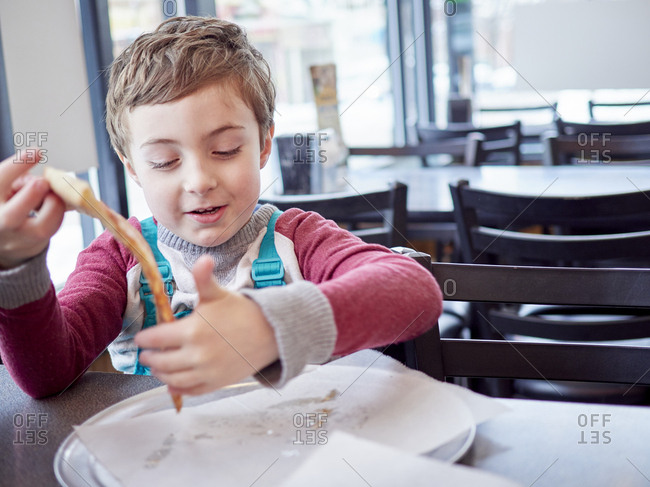 Boy picking up slice of pizza in restaurant