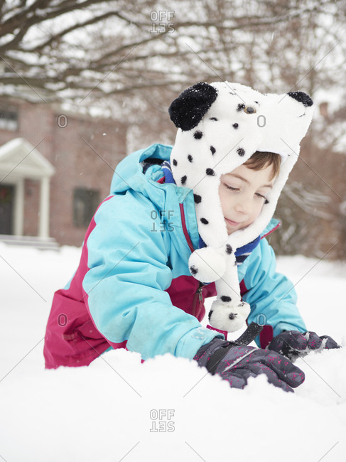 Boy wearing bear hat playing in snow