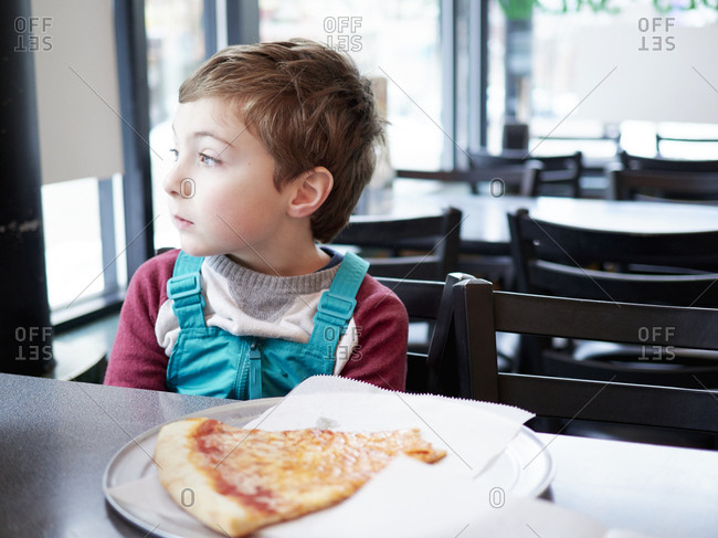 Boy gazes out window of pizzeria
