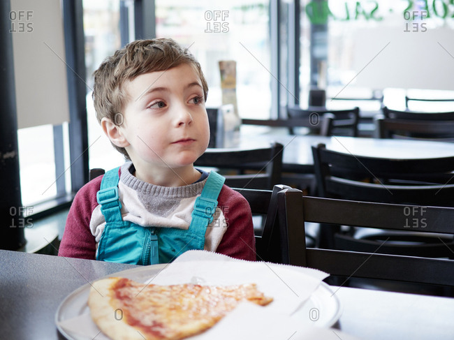 Young boy with slice of pizza in restaurant