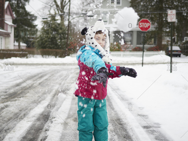 Boy throwing snowball on suburban street