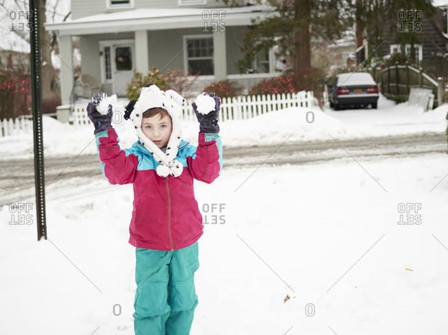 Boy in bear hat with two snowballs