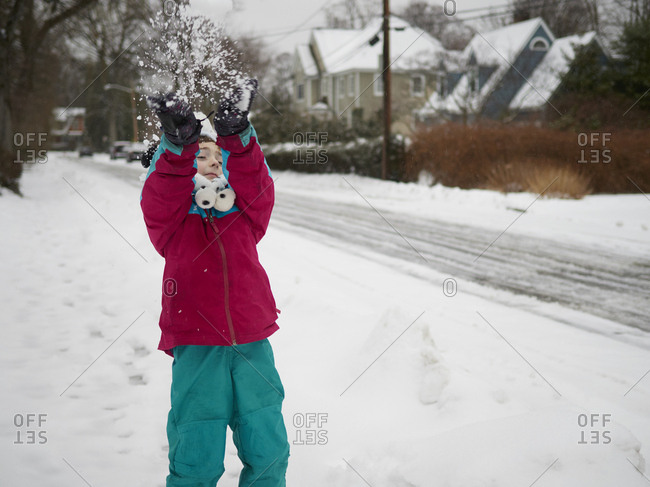 Boy playing in snow in suburban neighborhood