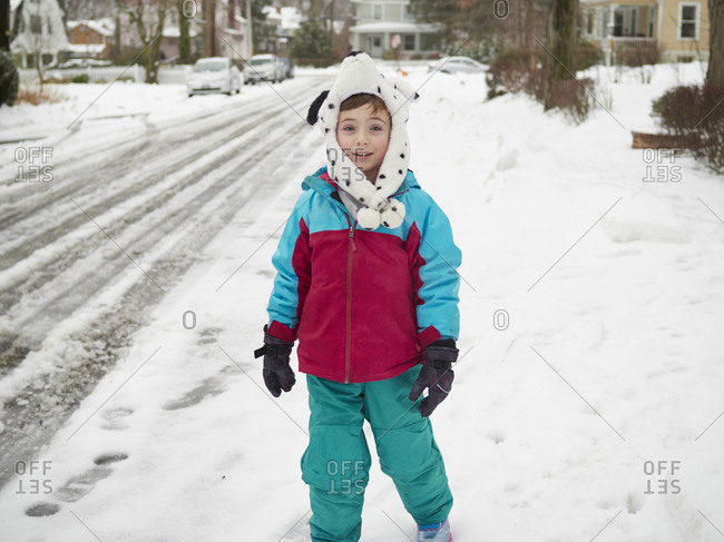 Portrait of boy in bear hat on snowy suburban street