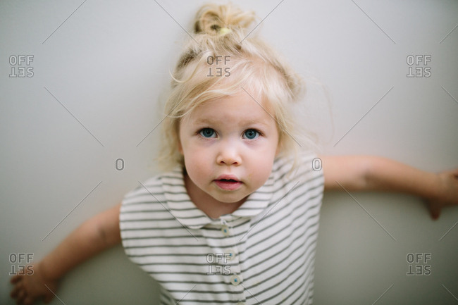 Toddler girl in striped dress standing against wall