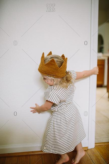 Toddler girl wearing crown running around wall