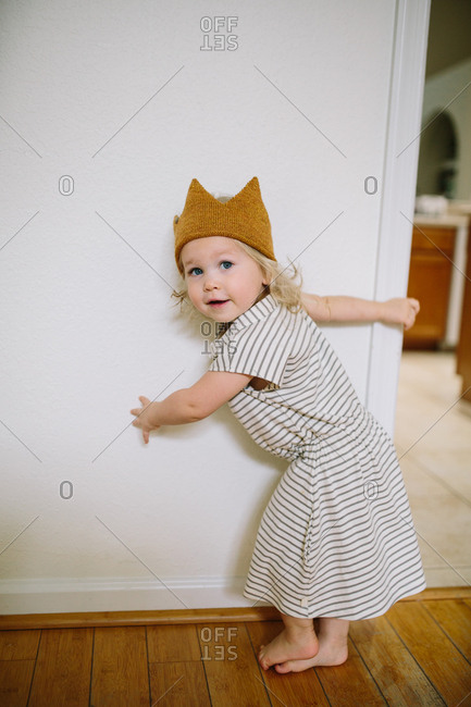 Toddler girl in crown playing in doorway