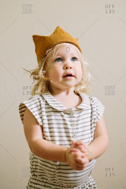 Portrait of a toddler girl with clasped hands and knitted crown hat