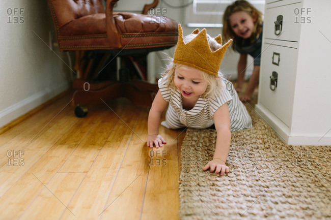 Toddler girl crawling on ground with sister