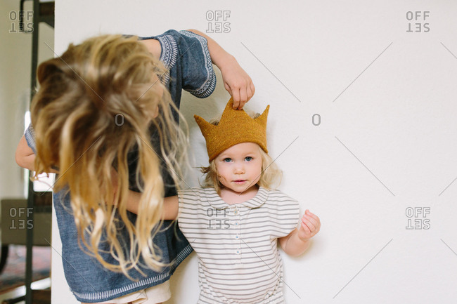 Big sister puts crown hat on toddler girl