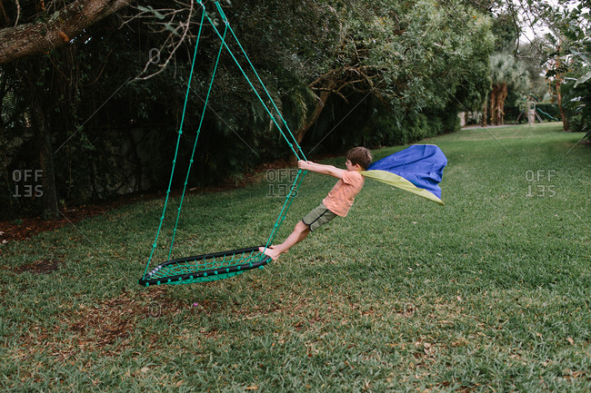 Boy in superhero cape playing on swing