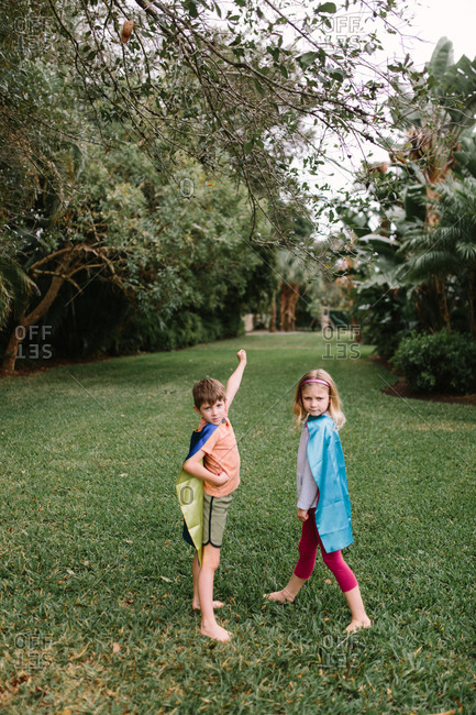 Two young siblings playing in superhero capes in backyard