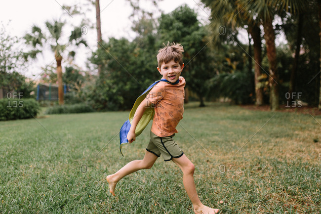 Boy in superhero cape running in backyard