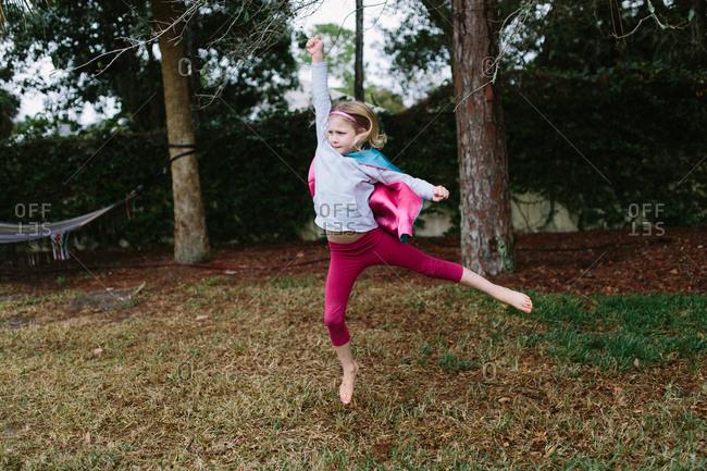Girl in superhero cape leaps in backyard