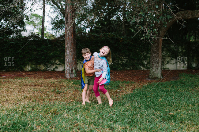 Siblings laughing together while wearing superhero capes
