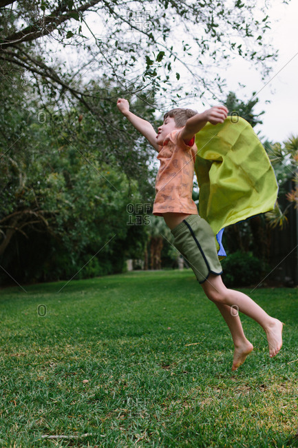 Boy wearing superhero cape leaps into the air