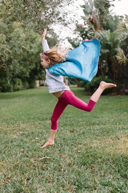 Girl in superhero cape pretending to fly