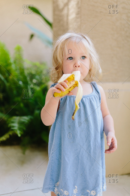 Little girl in blue dress eating a banana