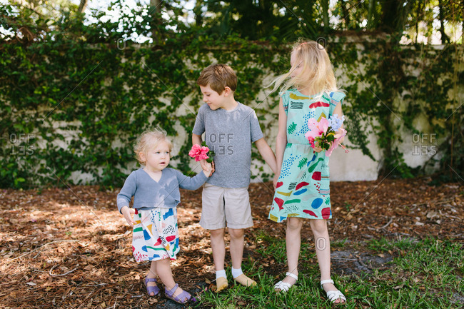 Siblings with flowers holding hands in backyard