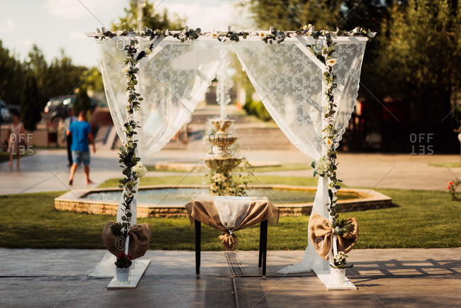 Wedding alter decorated with flowers and sheer fabric