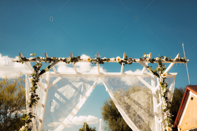 Arbor decorated with flowers and sheer fabric for a wedding