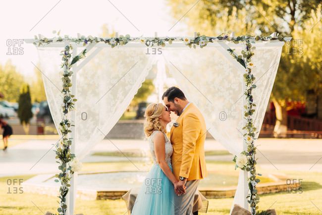 Bride and groom kissing under an alter with flowers and sheer fabric