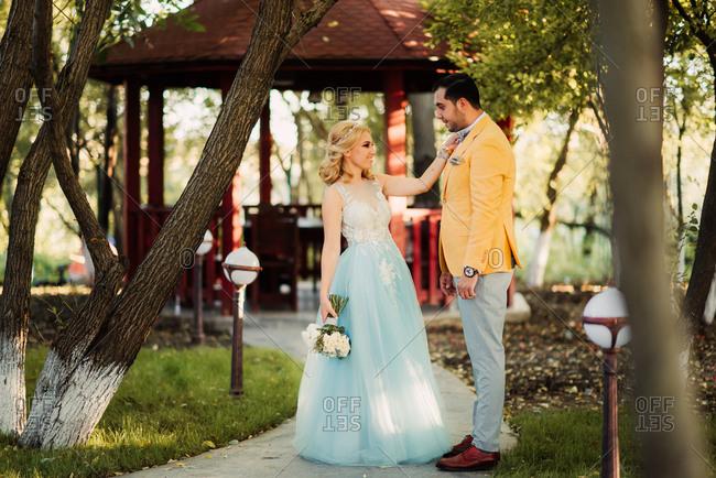 Bride adjusting groom's bowtie in a park