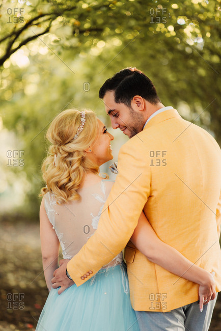 Rear view of newly married couple walking in a park