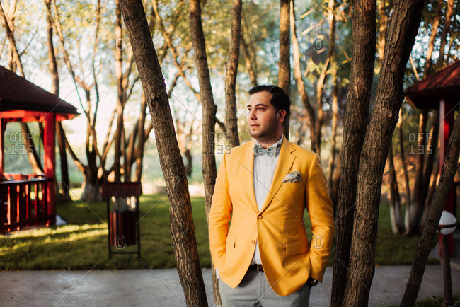 Groom wearing yellow jacket and bowtie standing in a park