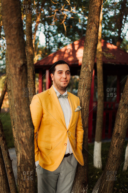 Groom wearing yellow jacket and bowtie standing by trees in a park