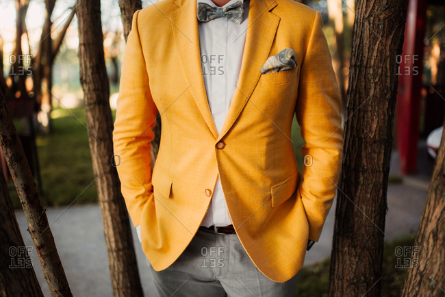Close up of a groom wearing yellow jacket and bowtie