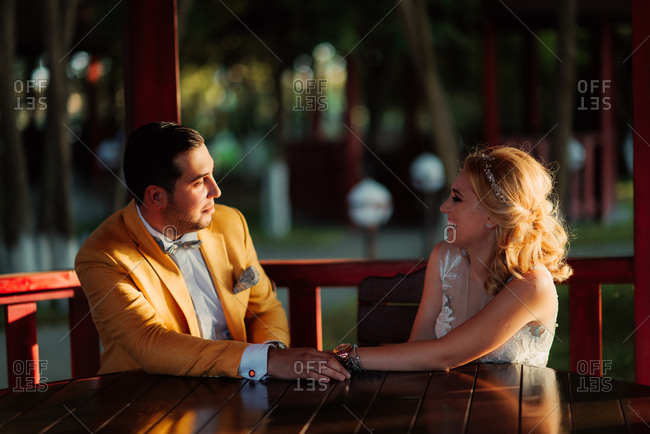 Newlywed couple holding hands while sitting in a gazebo