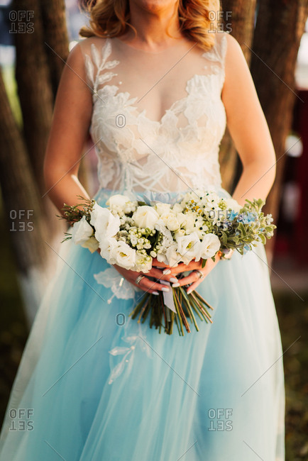 Bride wearing blue dress standing by trees in a park