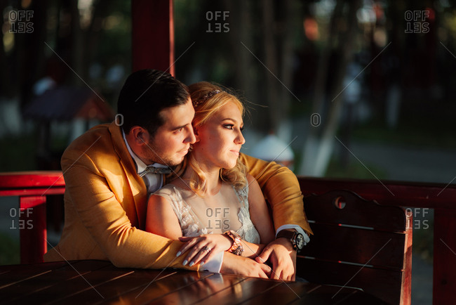 Newlywed couple embraced in a gazebo