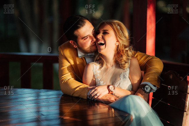Newlywed couple embraced and laughing in a gazebo