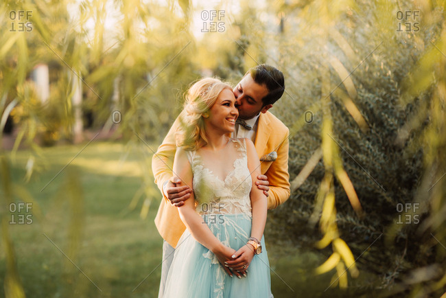 Groom kissing bride in a park by a willow tree