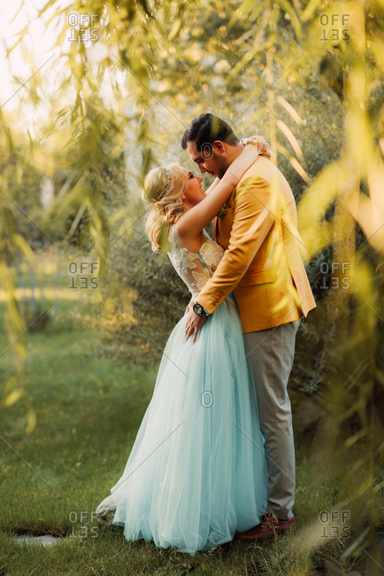 Bride and groom embraced in a park by a willow tree