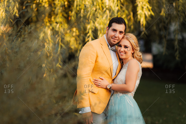 Bride and groom standing together in a park by a willow tree