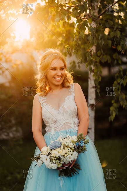 Portrait of bride holding a bouquet at sunset
