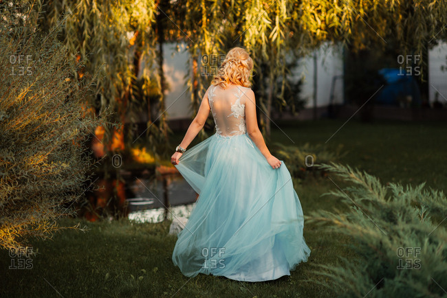 Rear view of bride twirling her blue dress by trees in a park