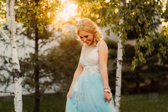 Bride twirling her blue dress by trees in a park