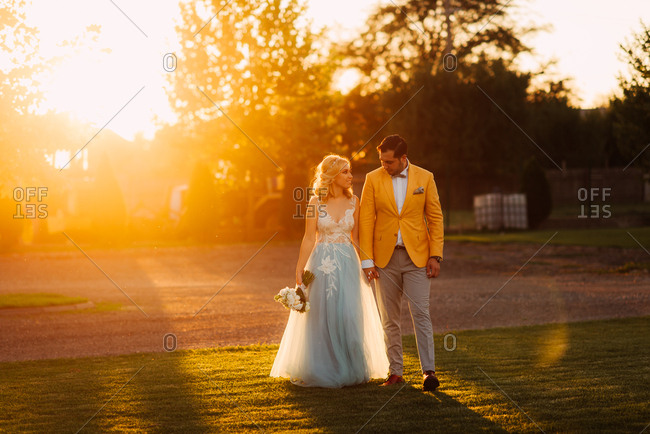 Groom walking hand in hand with bride at sunset