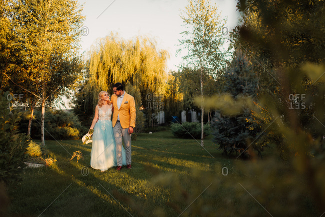 Groom walking with his arm around bride in a park at sunset