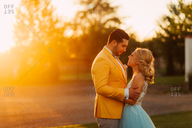 Newlywed couple in a field at sunset
