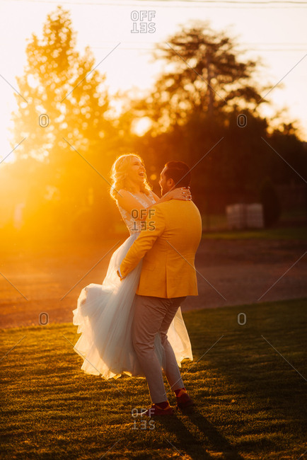 Groom picking up his bride at sunset