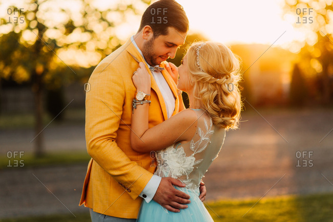 Young newlywed couple in a field at sunset