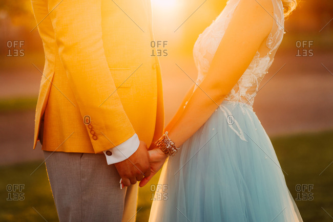 Close up of bride and groom holding hands at sunset