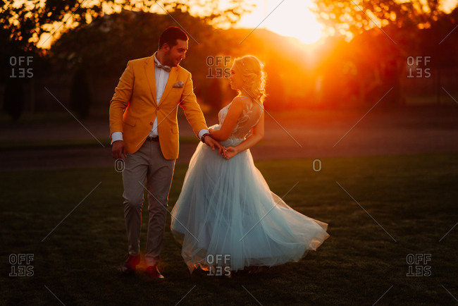 Newlywed couple dancing at sunset