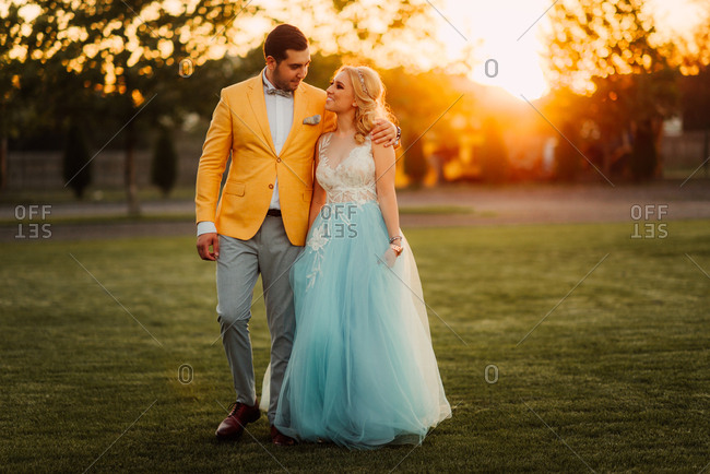 Young newlywed couple walking in a field at sunset